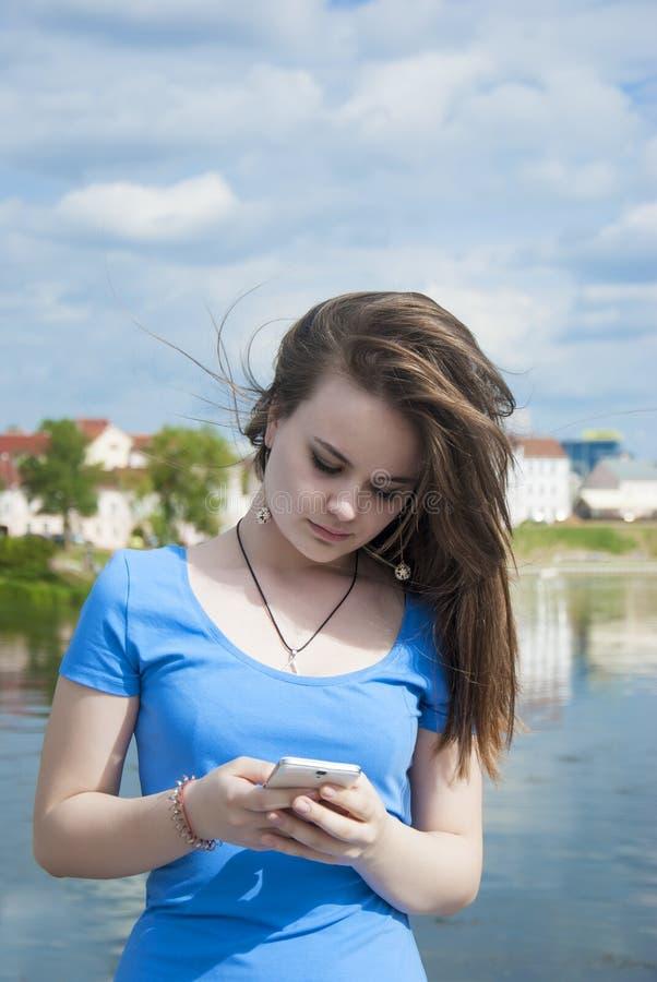 Schöne jugendlich Mädchenstände auf einem Stadthintergrund mit einem Handy sendet eine Mitteilung stockfoto