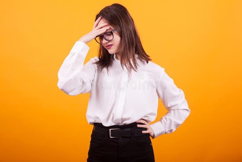 Schöne Jugendliche, die eine Migräne im Studio über gelbem Hintergrund hat stockfoto