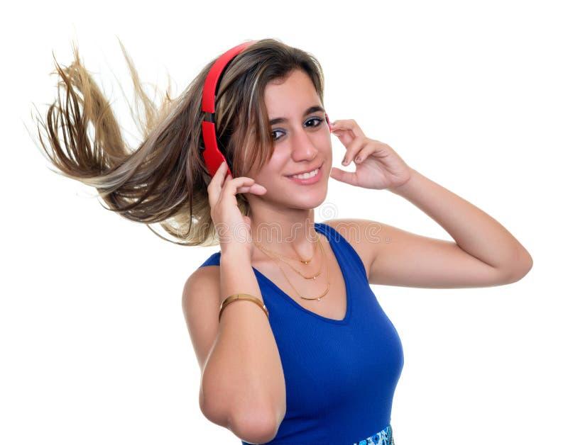 Schöne Jugendliche, die an Musik mit ihrem Haarfloss hört stockbilder