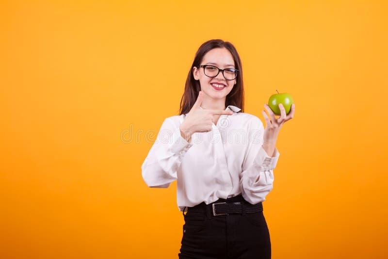 Schöne Jugendliche mit den Brillen, die einen grünen Apfel halten und auf ihn zeigen lizenzfreie stockbilder