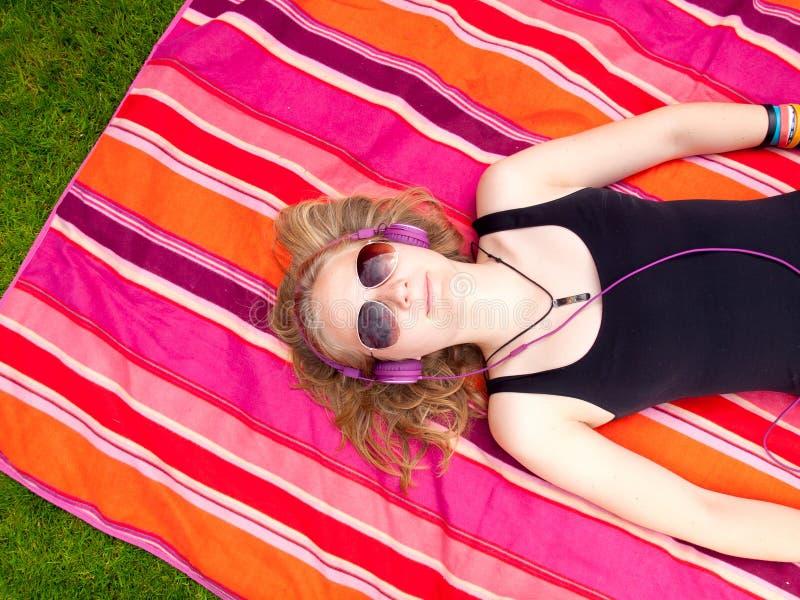 Schöne Jugendliche mit den Kopfhörern, die zurück auf ihr liegen lizenzfreie stockbilder