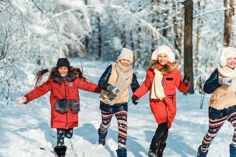 Schöne Jugendlichen, die Spaßaußenseite in einem Holz mit Schnee im Winter haben Freundschaft und Berufslebenkonzept lizenzfreie stockbilder