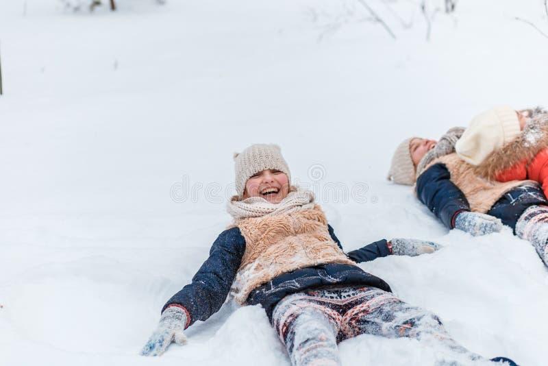 Schöne Jugendlichezwillingsschwestern, die Spaßaußenseite in einem Holz mit Schnee im Winter haben Freundschaft, Familie, Konzept stockbilder
