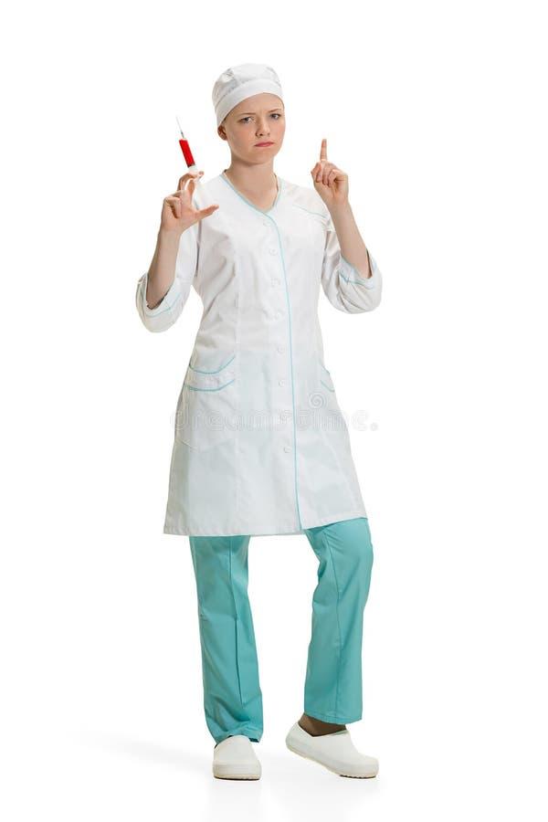 Schöne junge Ärztin in der medizinischen Robe, die in der Hand Spritze hält lizenzfreies stockfoto