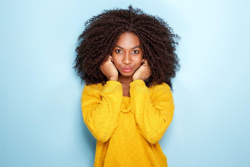Schöne junge afrikanische Frau, die Ohren auf blauem Hintergrund hält lizenzfreies stockfoto