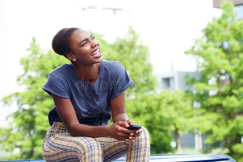 Schöne junge Afroamerikanerfrau, die draußen mit Handy lacht lizenzfreie stockbilder