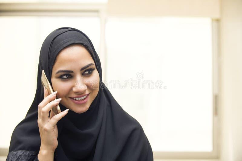 Schöne junge arabische Frau, die am Handy spricht lizenzfreie stockfotografie