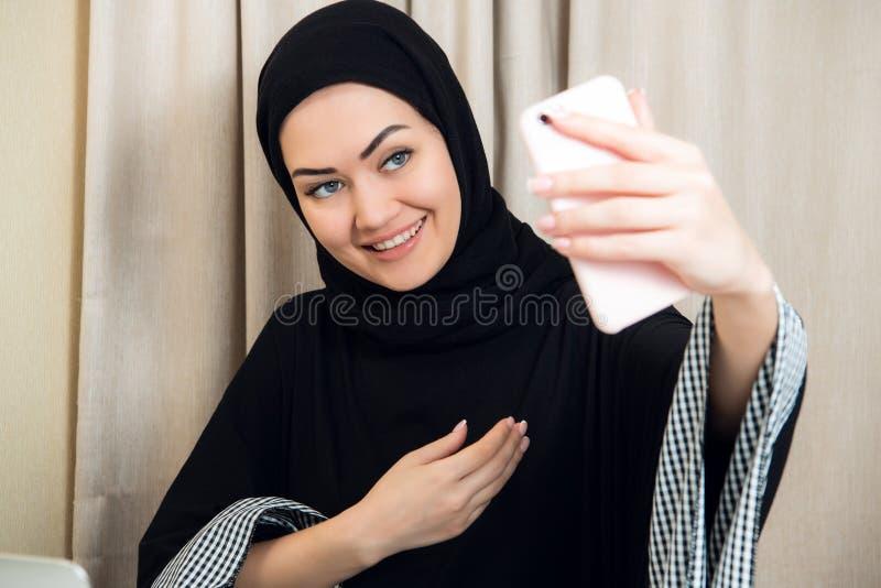 Schöne junge arabische Frau, die selfie mit ihrem Handy nimmt stockfoto