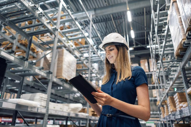 Schöne junge Arbeitnehmerin des Möbelgeschäfts im Einkaufszentrum Das Mädchen, das nach Waren mit einer Tablette sucht, überprüft lizenzfreies stockbild