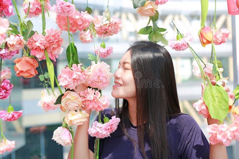 Schöne junge Asiatin, die mit Blumen in einem Garten aufwirft stockbild