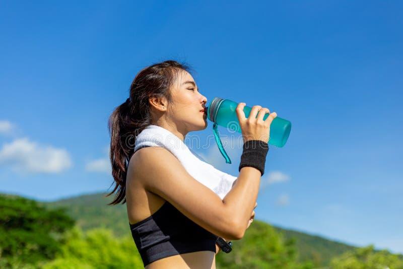 Schöne junge Asiatin, die morgens an einer Laufbahn, eine Pause machend, um Wasser zu trinken trainiert stockbilder