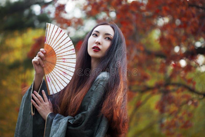 Schöne junge Asiatin mit Fan auf Hintergrund des Rotahorns stockfoto