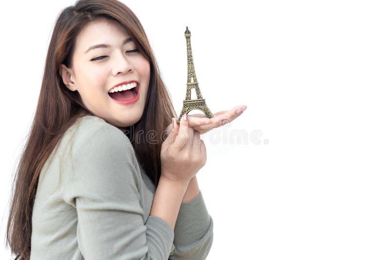 Schöne junge asiatische Frau des Glückes, die in der Hand Metall wenig Eiffelturmmodell lokalisiert auf weißem Hintergrund hä stockfotografie