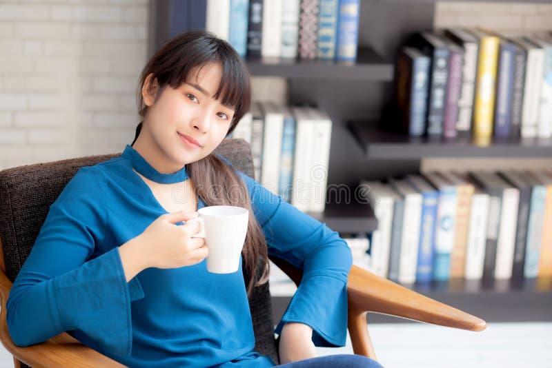 Schöne junge asiatische Frau, die auf Stuhl mit Komfort sitzt und sich zu Hause im Wohnzimmer trinkt einen Tasse Kaffee entspann stockfoto