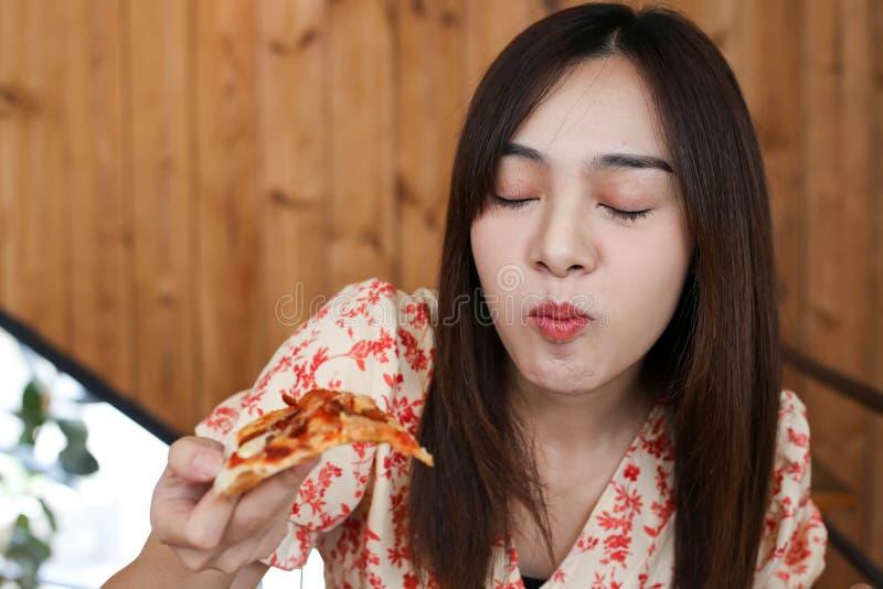 Schöne junge asiatische Frau, die köstliche oder leckere Pizza isst stockfotografie