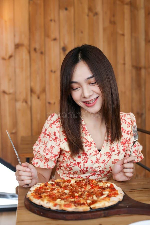 Schöne junge asiatische Frau, die köstliche oder leckere Pizza isst stockfoto