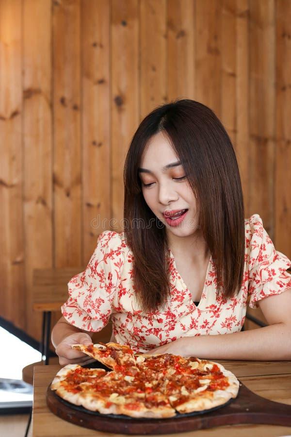Schöne junge asiatische Frau, die köstliche oder leckere Pizza isst stockfotos