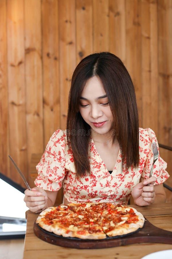 Schöne junge asiatische Frau, die köstliche oder leckere Pizza isst lizenzfreies stockfoto