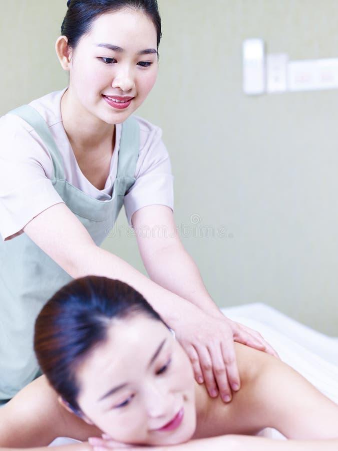Schöne junge asiatische Frau, die Massage im Badekurortsalon empfängt stockfotografie