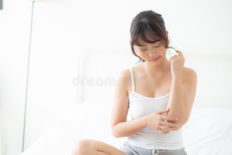 Schöne junge asiatische Frau, die skincare und Feuchtigkeitscremecreme oder -behandlung für Kratzer anwendet stockfotos