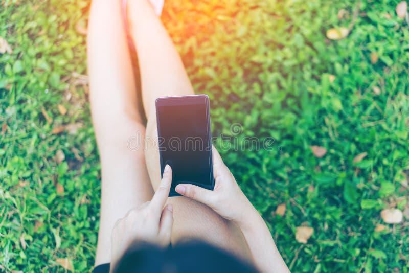 Schöne junge asiatische Frau, die Smartphone im Garten verwendet lizenzfreie stockbilder