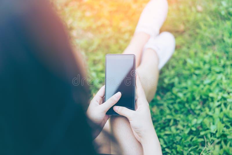 Schöne junge asiatische Frau, die Smartphone im Garten verwendet lizenzfreies stockfoto