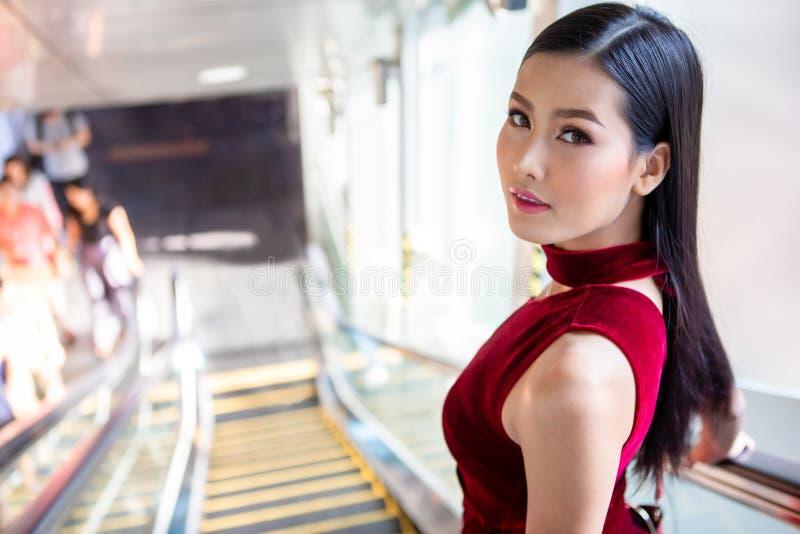 Schöne junge asiatische Frau im roten Kleid, das die Rolltreppe im Einkaufszentrum hinuntergeht Gl?ckliche elegante Dame Kopieren stockfotos
