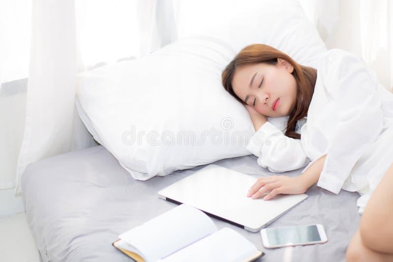 Schöne junge asiatische Frau mit dem Laptop, der sich im Schlafzimmer hinlegt, Mädchen ermüdete Schlaf mit Computernotizbuch stockbilder