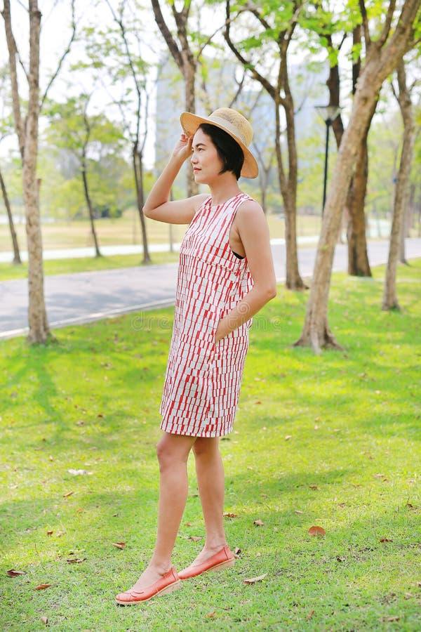 Schöne junge asiatische Frau wirft im Naturpark auf lizenzfreie stockfotos