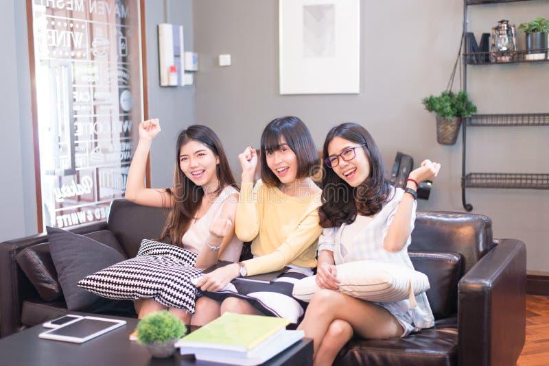 Schöne junge asiatische Freundinnen, die das Unterhaltungsc$lächeln des Tablet-Computers und das Lachen verwenden stockbild