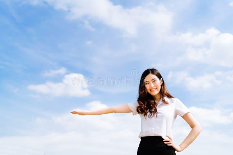 Schöne junge asiatische Hochschul- oder Studentfrau, die Werbung tun oder Produkt, das Haltung, Kopienraum auf BAC des blauen Him stockfoto