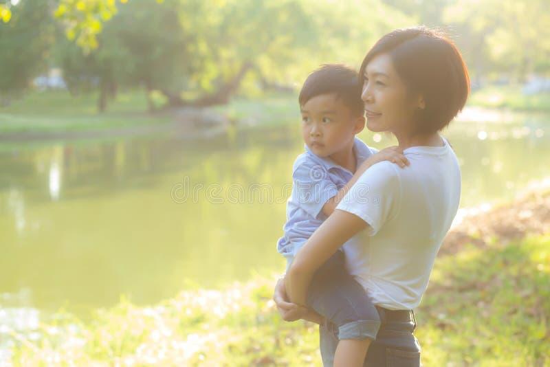 Schöne junge asiatische Mutter, die wenig Jungen im Park, Asien-Frau glücklich trägt, Sohn und Umarmungskind habend lizenzfreie stockbilder