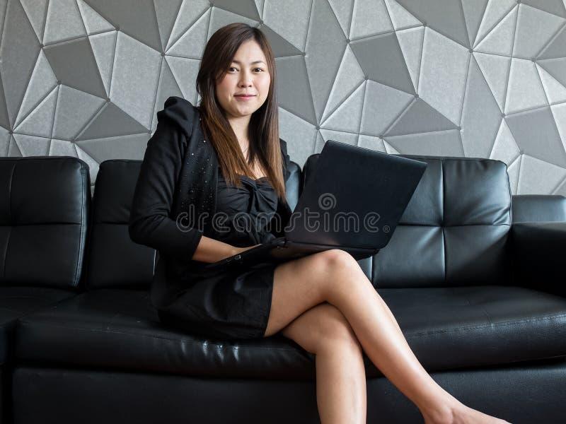 Schöne junge Asien-Geschäftsfrau, die auf Sofa, arbeitend mit der Laptop-Computer und Abnutzungsschwarzanzug aufpassen zur Kamera lizenzfreies stockfoto