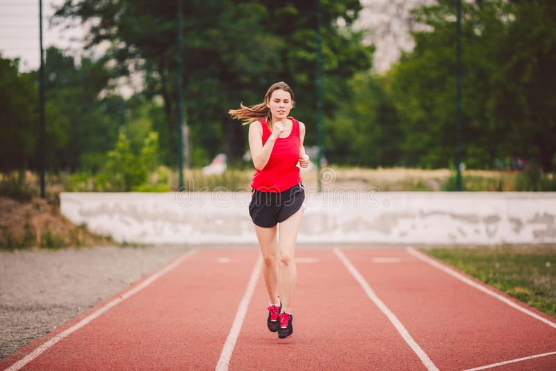 Schöne junge Athlet Caucasian-Frau mit den großen Brüsten im roten T-Shirt und in den kurzen kurzen Hosen Rütteln, laufend in das lizenzfreie stockfotografie