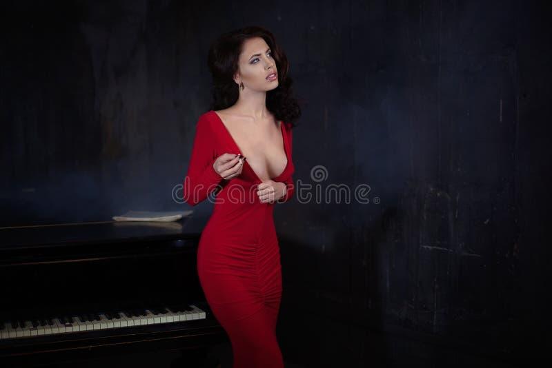 Schöne junge attraktive Frau, wenn rotes Kleid und Klavier geglättet werden stockfoto