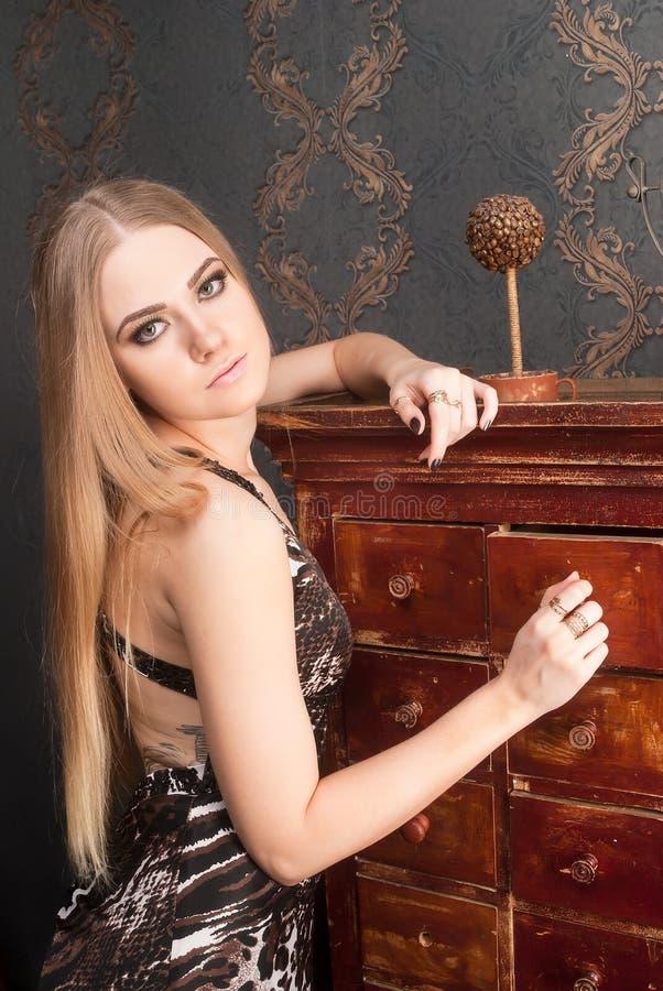 Schöne junge blonde behaarte Frau öffnet Fach lizenzfreie stockbilder