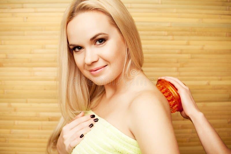 Schöne junge blonde Frau, die Körpermassage empfängt stockfotografie