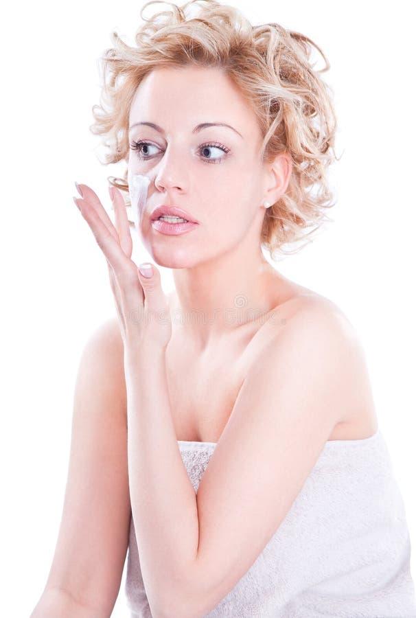 Schöne junge blonde Frau, die Sahne aufträgt lizenzfreie stockfotografie