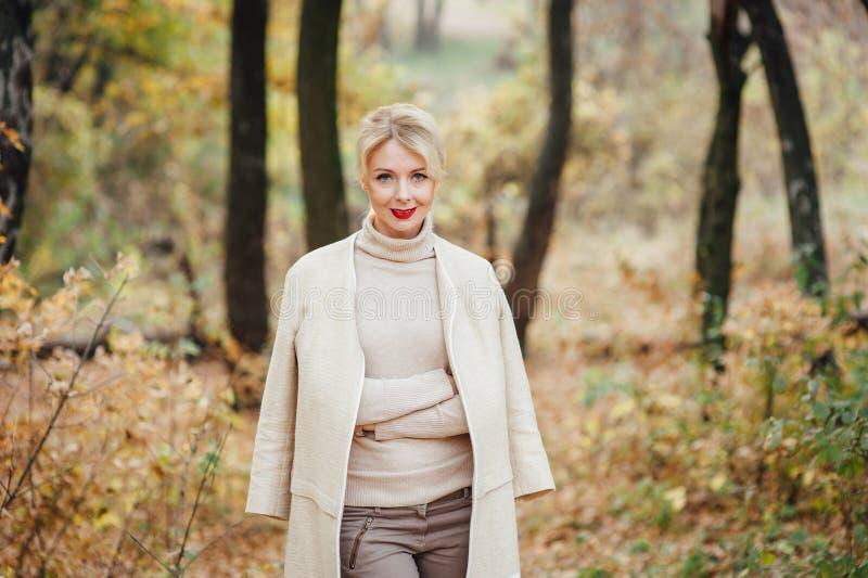 Schöne junge blonde Frau, die Zeit im Herbstpark verbringt lizenzfreies stockfoto