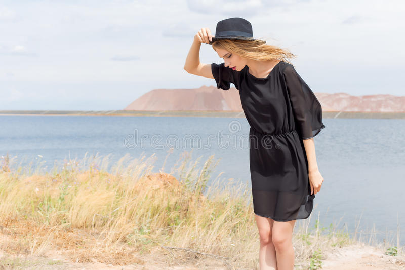 Schöne junge blonde Frau in einem schwarzen Kleid und in einem hellen schwarzen Hut in der Wüste und der Wind, der ihr Haar an ei lizenzfreie stockfotos