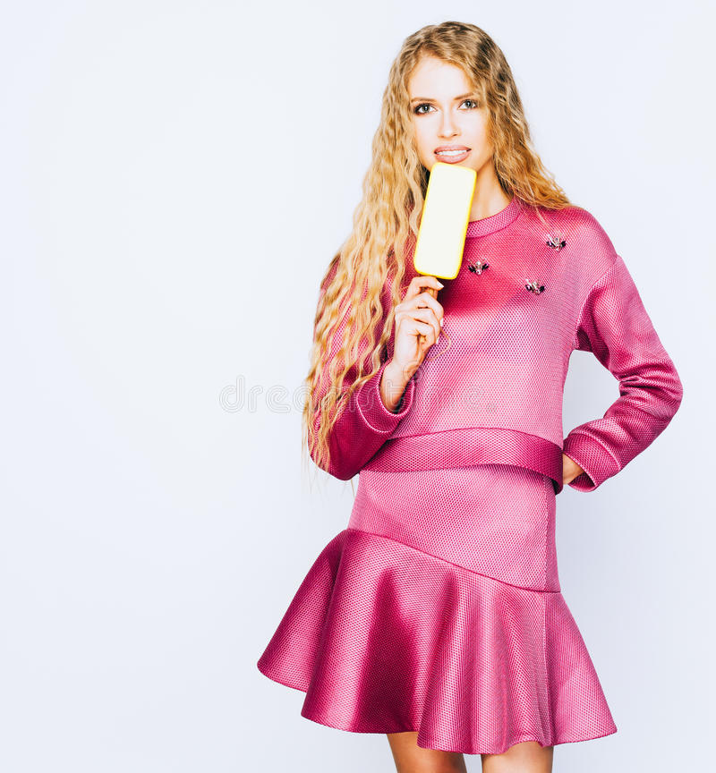 Schöne junge blonde Frau im modernen purpurroten Kleid Eis am Stiel essend stockfotos