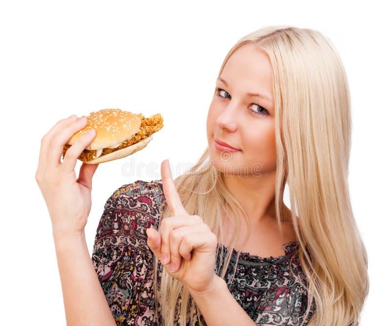 Schöne junge blonde Frau mit einem Burger, lokalisiert gegen Whit lizenzfreies stockfoto