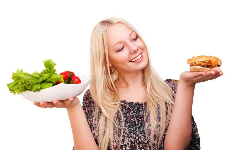 Schöne junge blonde Frau mit einem Burger und einem Salat stockfotos