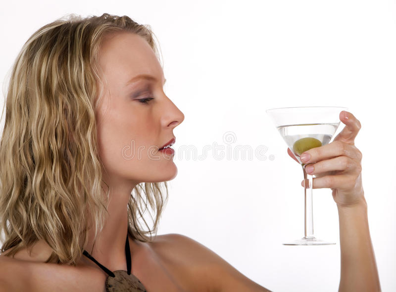 Schöne junge blonde Frau mit einem Martini-Getränk stockfoto