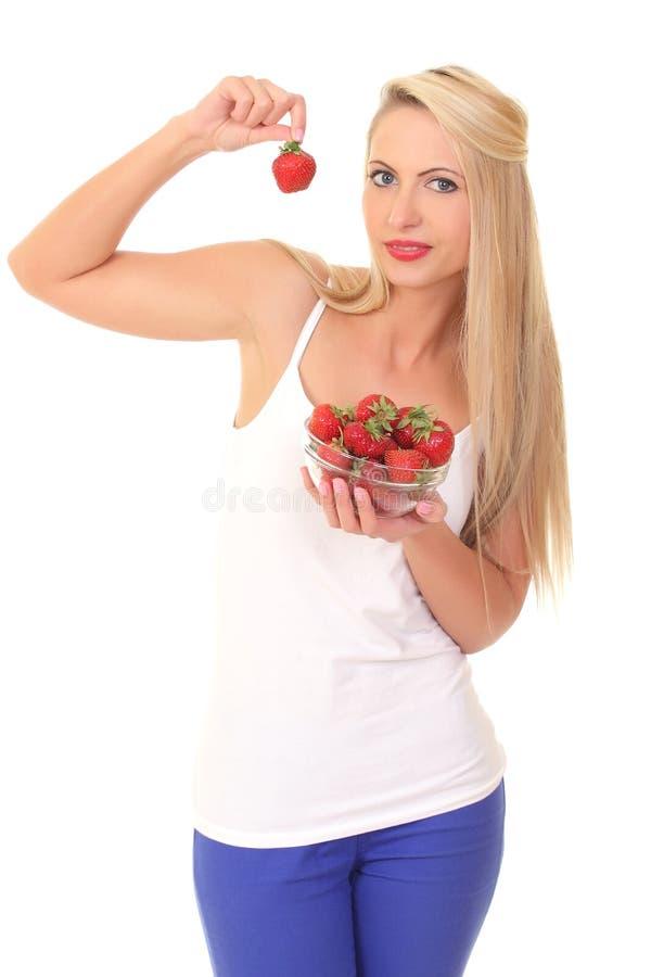 Schöne junge blonde Frau mit Erdbeere stockfotografie