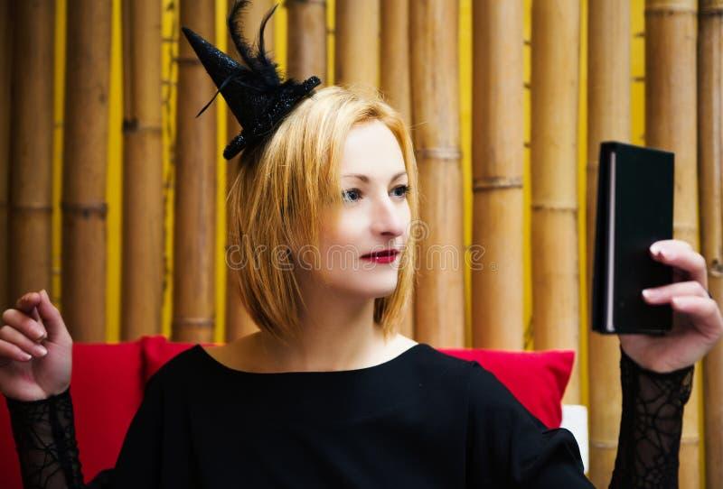 Schöne junge blonde Hexe in einem Café an einem Feiertag Halloween lizenzfreies stockfoto