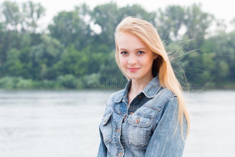 Schöne junge Blondine in den Blue Jeans mit dem Lächeln, das Kamera auf Natur betrachtet lizenzfreies stockfoto