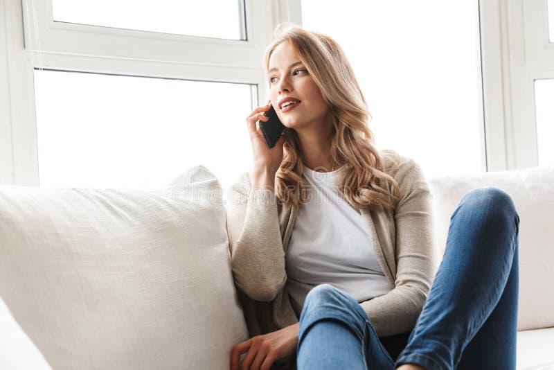 Schöne junge Blondine, die auf einer Couch sich entspannen lizenzfreies stockbild