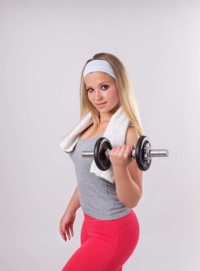 Schöne junge Blondine, die mit Dummköpfen trainieren stockfotos