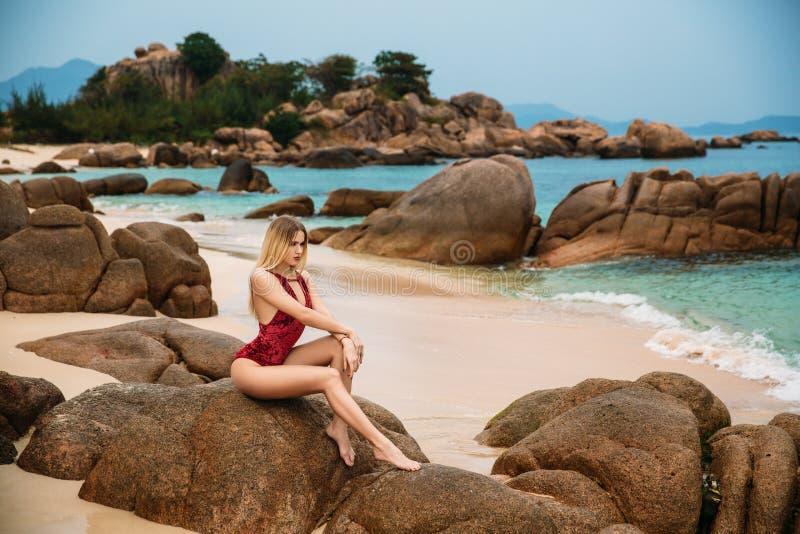 Schöne junge Blondine im roten Bikini, der auf dem Strand aufwirft Sexy vorbildliches Porträt mit perfektem Körper Konzept des So lizenzfreie stockfotos